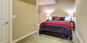 Basement guest bedroom without windows with blue and red bedding.